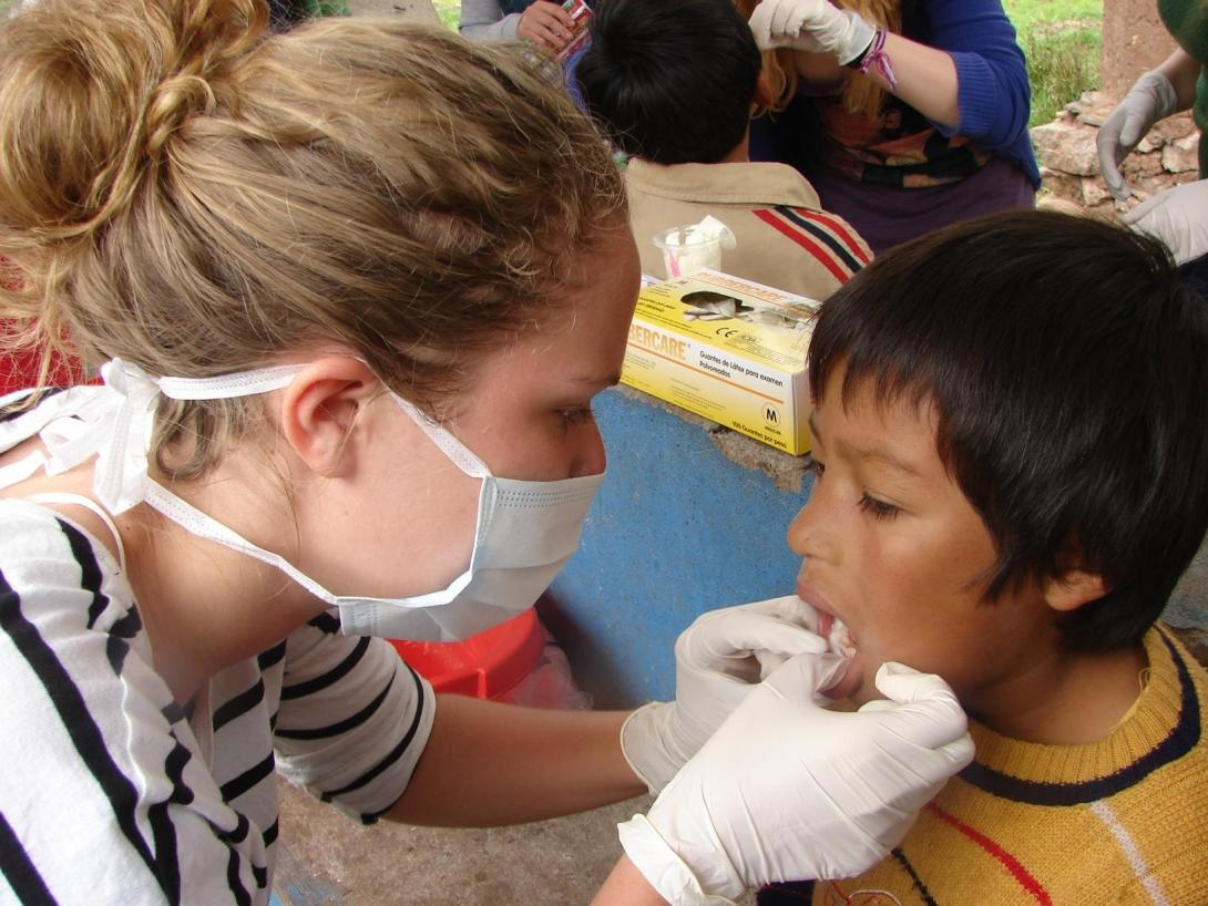 Projects Abroad volunteer checks the dental health of a young boy during a medical outreach in Peru.